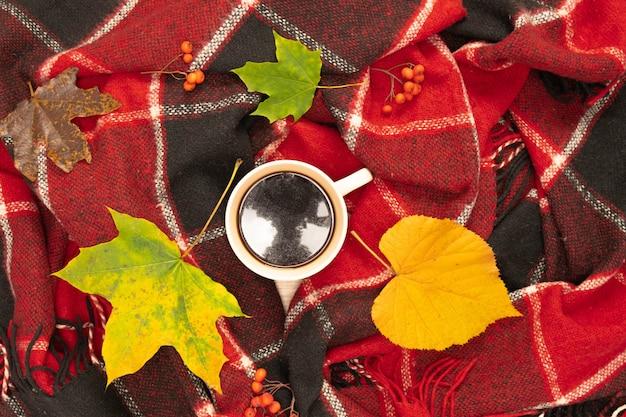 Composition d'automne avec une tasse de café aux feuilles lumineuses sur un plaid à carreaux rouge. filmé d'en haut. place pour votre texte.