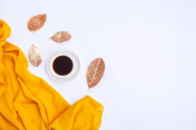 Composition d'automne. tasse de café, écharpe jaune, feuilles sèches sur fond blanc. automne, concept d'automne. mise à plat, vue de dessus, espace de copie