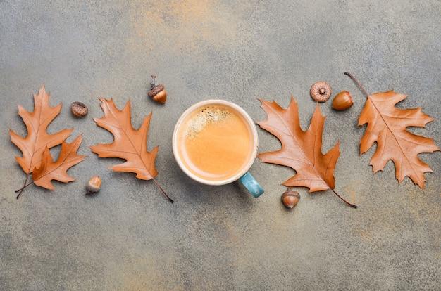 Composition d'automne avec une tasse de café et des feuilles d'automne sur fond de pierre ou de béton