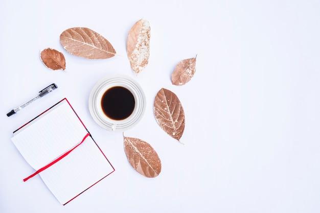 Composition d'automne. tasse de café, feuilles sèches, livre et stylo sur fond blanc. automne, concept d'automne. mise à plat, vue de dessus, espace de copie