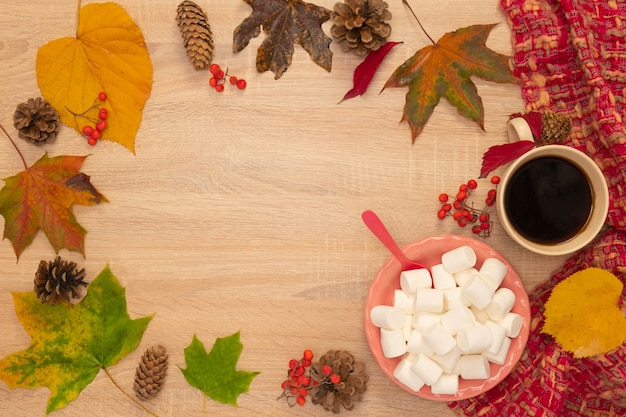 Composition d'automne avec une tasse de café, des guimauves et des feuilles. tourné d'en haut sur un fond en bois. place pour votre texte.