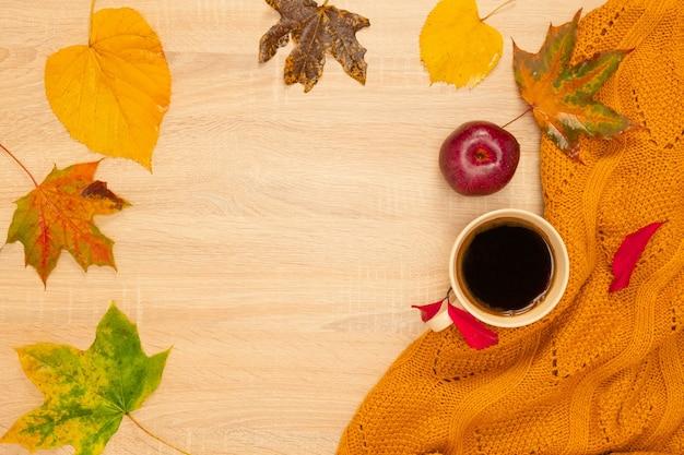 Composition d'automne avec une tasse de café, des guimauves, un pull et des feuilles. tourné d'en haut sur un fond en bois. place pour votre texte.