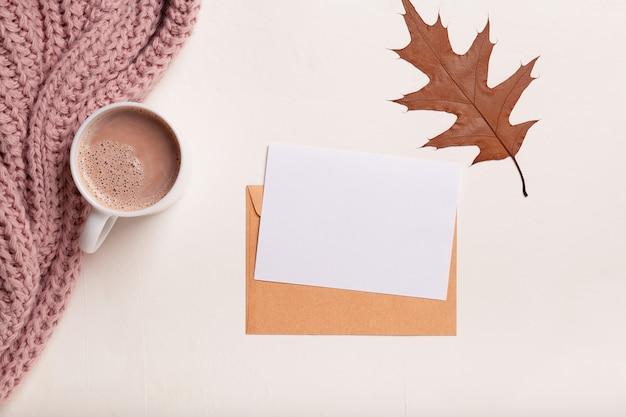 Composition d'automne, tasse de café, plaid rose et papier blanc sur fond blanc plat poser