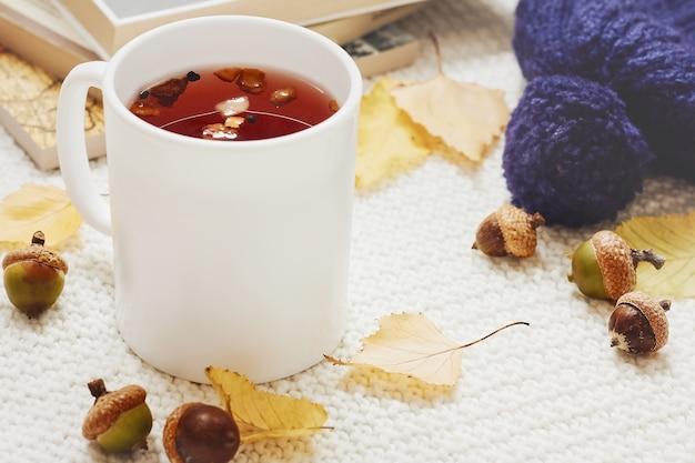 Composition d'automne. tasse de thé, feuilles d'automne, glands, chapeau chaud et pile de livres