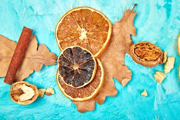 Composition d'automne avec des tranches d'oranges séchées, de feuilles et de cannelle.
