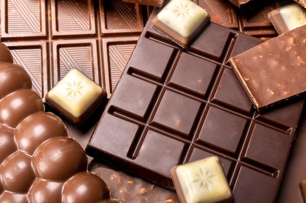 Composition de barres et morceaux de différents chocolats au lait et noir. différents types de délicieux chocolat vue de dessus