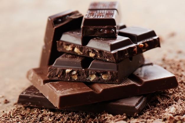 Composition de barres et de morceaux de différents lait et chocolat noir, cacao râpé sur un fond brun vue de côté close up