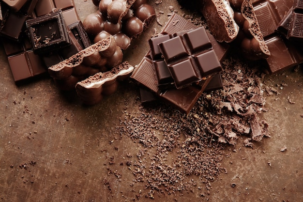Composition de barres et de morceaux de différents lait et chocolat noir, cacao râpé sur un fond brun vue de dessus close up