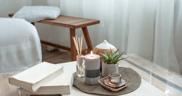 Composition avec bâtons d'encens, diffuseur, bougies et livres sur la table à l'intérieur de la pièce.