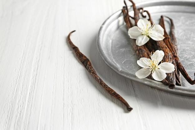 Composition avec des bâtons de vanille séchée sur table en bois clair, gros plan