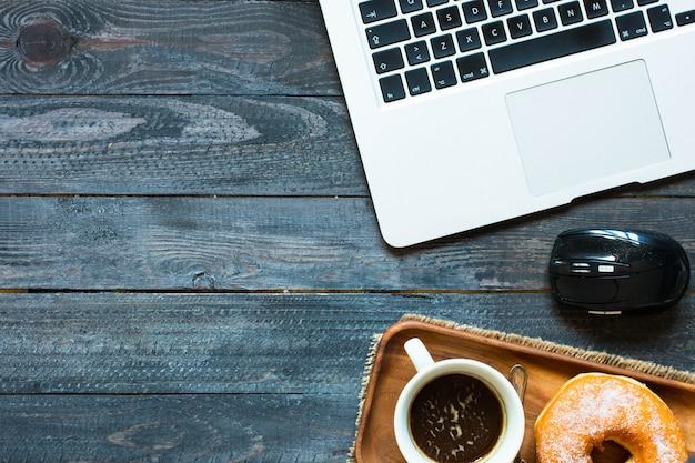Composition de beignets colorés avec ordinateur portable et tasse à café