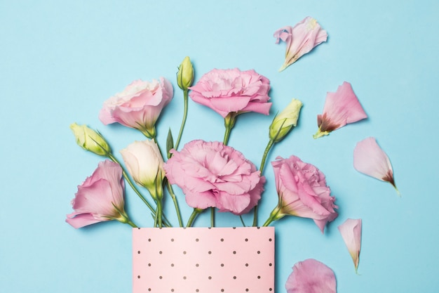 Composition de belles fleurs roses fraîches en paquet de papier près des pétales