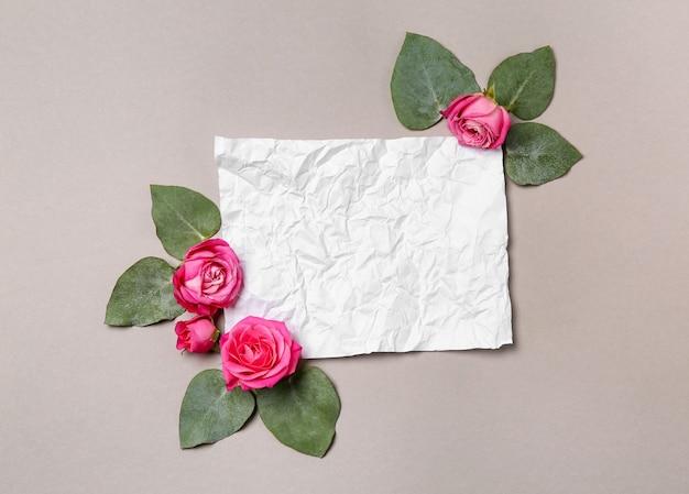 Composition avec de belles roses roses et carte de papier froissé sur fond gris