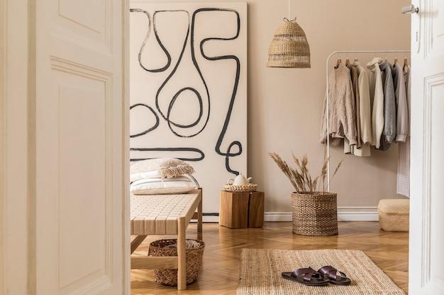 Composition bohème du salon avec chaise longue design, oreillers, paniers, peinture, cintre, décorations naturelles en rotin et accessoires personnels élégants.