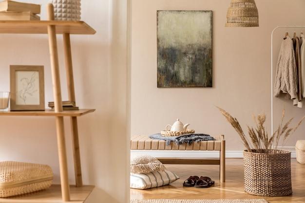 Composition bohème du salon avec chaise longue design, oreillers, paniers, peinture, décorations naturelles en rotin et accessoires personnels élégants.