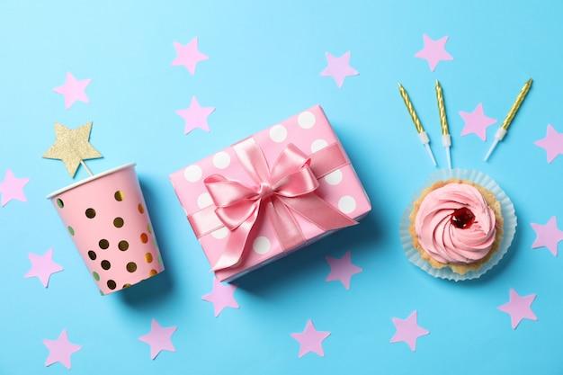 Composition avec boîte-cadeau et cupcake sur fond bleu, vue de dessus