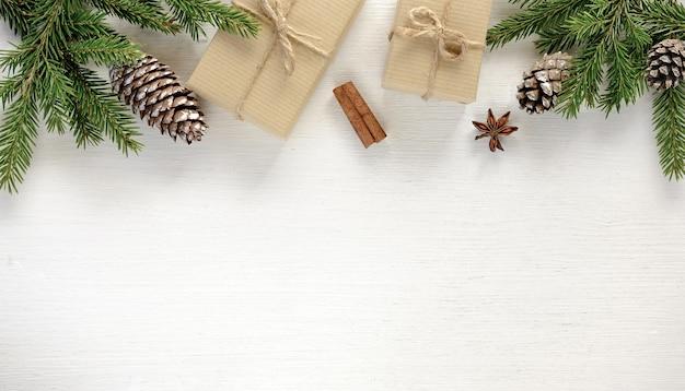 Composition de bordure de noël faite de branches de sapin, coffrets cadeaux de cônes emballés dans du papier kraft sur fond de bois blanc. mise à plat, vue de dessus, espace de copie