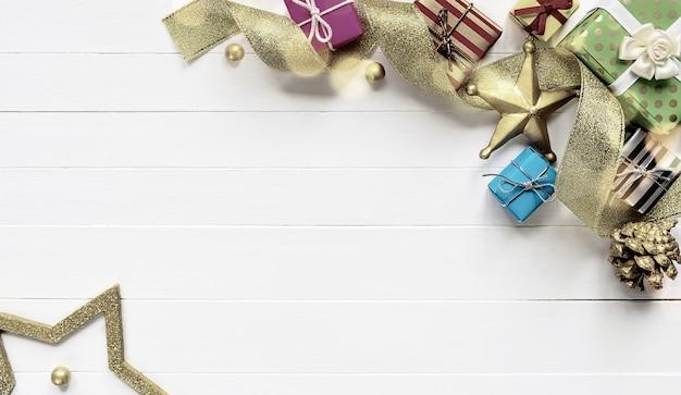 Composition de bordure de noël faite de coffrets cadeaux ruban d'or et boules sur table en bois blanc. mise à plat, espace de copie. style rétro tonique