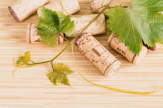 Composition de bouchons de vin avec vigne sur table en bois.