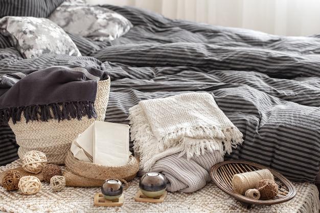 Composition avec bougies, éléments tricotés et autres détails de décoration dans la chambre.
