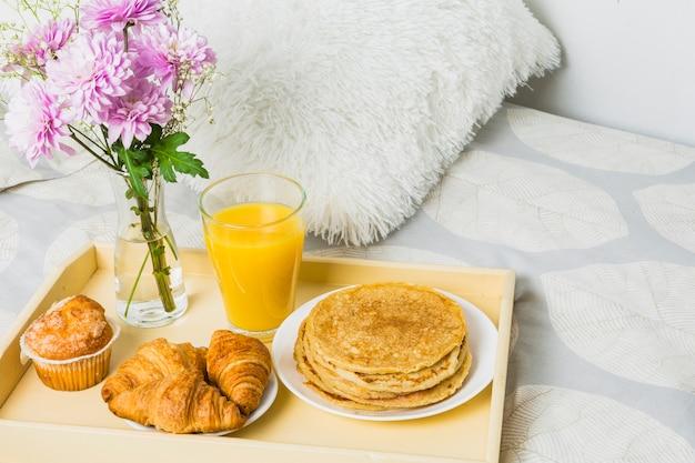 Composition de boulangerie, verre et fleurs sur plateau sur lit