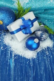 Composition avec boules de noël, coffret cadeau et neige sur fond de bois de couleur