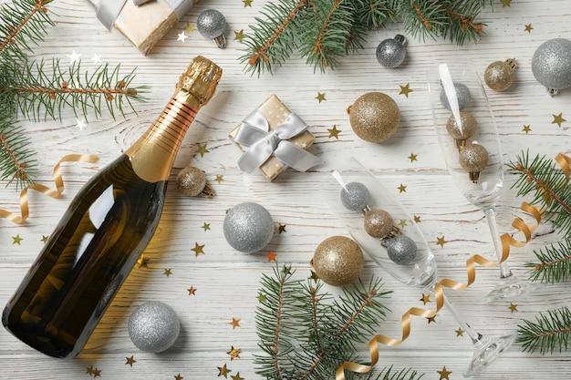 Composition avec des boules de noël et du champagne sur un espace en bois blanc, vue de dessus