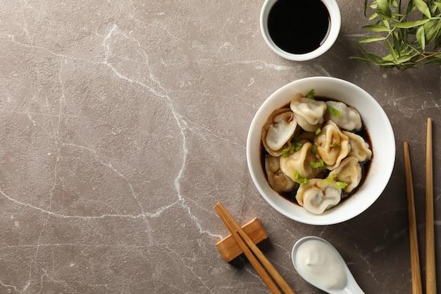 Composition avec boulettes, baguettes et sauce soja sur fond gris, vue de dessus