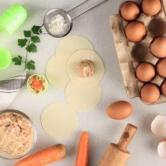 Composition avec des boulettes crues (dim sum) et des ingrédients sur fond de marbre blanc. copiez l'espace pour le texte, processus de cuisson faisant shumay, dimsum chinois cuit à la vapeur