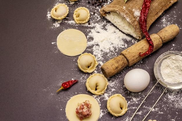 Composition avec des boulettes crues et des ingrédients sur fond de béton en pierre noire à la mode. processus de cuisson