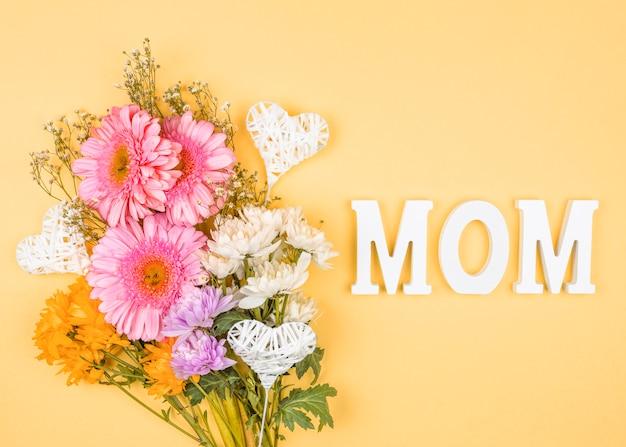 Composition de bouquet de fleurs fraîches près de coeurs d'ornement sur baguettes et mot de maman