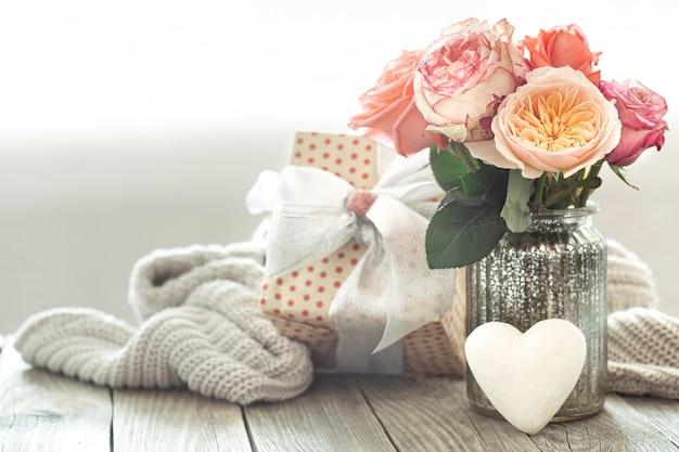 Composition avec un bouquet de roses dans un vase en verre avec un coffret cadeau