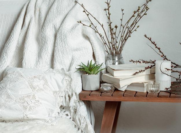 Composition avec des branches de printemps, des livres et des bougies à l'intérieur de la pièce.