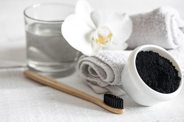 Composition avec brosse à dents naturelle en bois et poudre noire pour le blanchiment des dents.
