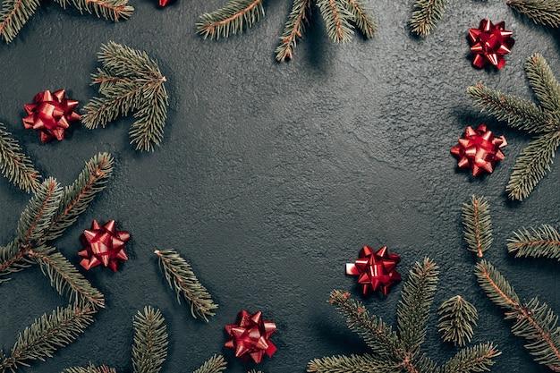 Composition de cadre de noël minimale avec branche de sapin et arcs rouges sur fond sombre. nouvelle année