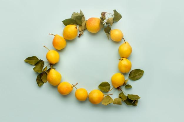 Composition de cadre rond d'automne de poires jaunes mûres avec des feuilles sur un bleu pastel