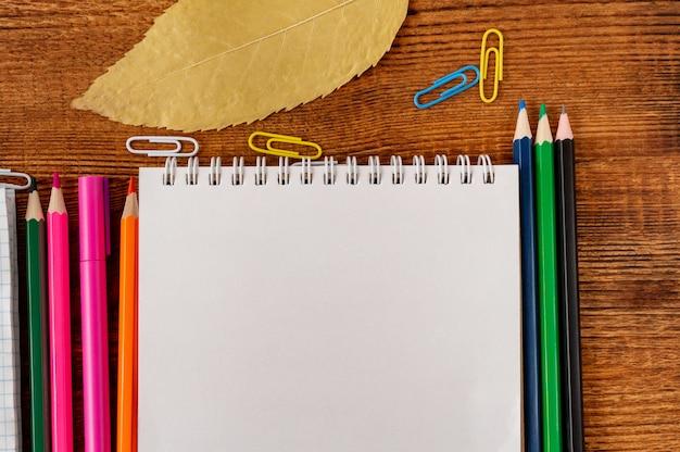 Composition avec cahier coloré de page blanche de cahier, marqueur et maquette de stylo retour au concept de l'école