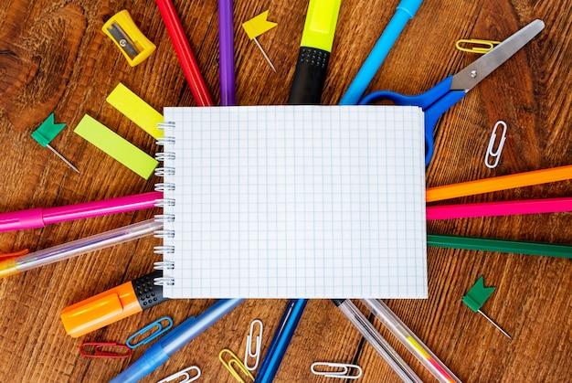 Composition avec cahier page vierge, crayon coloré, marqueur et maquette de stylo retour au concept de l'école