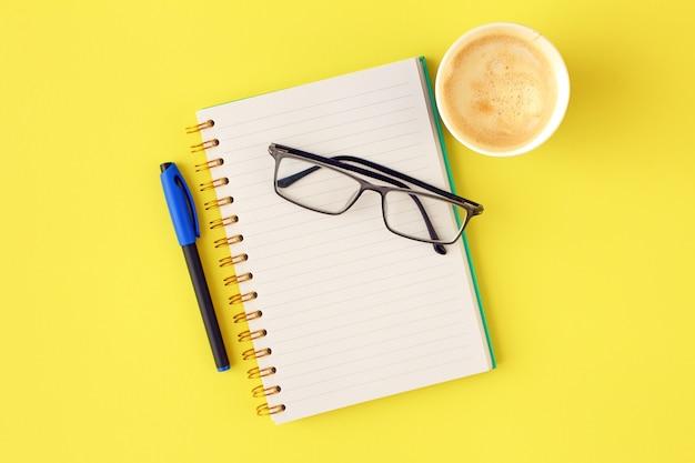 Composition de cahier, stylo, lunettes, tasse de café sur fond jaune pastel.