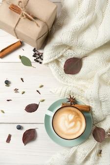 Composition de cappuccino d'automne. vue de dessus de tasse à café bleu avec mousse, clous de girofle, cannelle, boîte cadeau et chandail chaud à table en bois blanc sur feuille de papier. concept de boissons chaudes d'automne