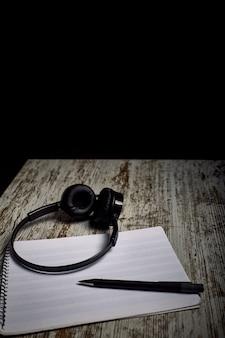 Composition d'un casque noir à côté d'un cahier de pentagramme vide sur une table en bois