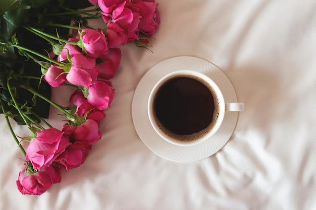 Composition chaleureuse matinée à plat avec des fleurs et une tasse de café petit-déjeuner au lit