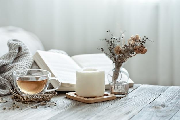Une composition chaleureuse avec une tasse de thé, un livre et des détails de décoration à l'intérieur de la pièce sur un fond flou.