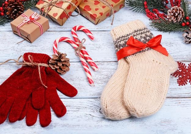 Composition de chaussettes chaudes et de gants avec des décorations de noël sur fond de bois blanc