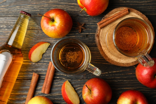 Composition avec cidre, cannelle et pommes sur table en bois