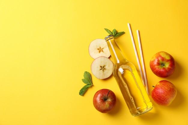 Composition avec cidre, pommes et pailles sur jaune