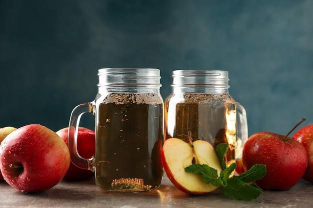 Composition avec cidre et pommes sur table grise