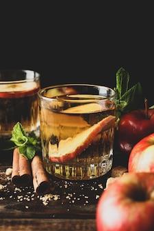 Composition avec cidre, sucre, cannelle et pommes sur table en bois
