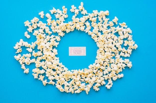 Composition circulaire de popcorn avec billet de film