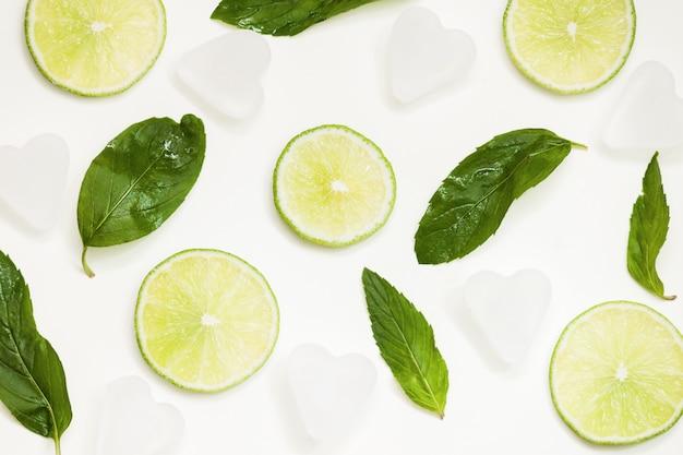 Composition avec citron vert frais, feuilles de menthe, glace sur fond clair, vue de dessus, gros plan.